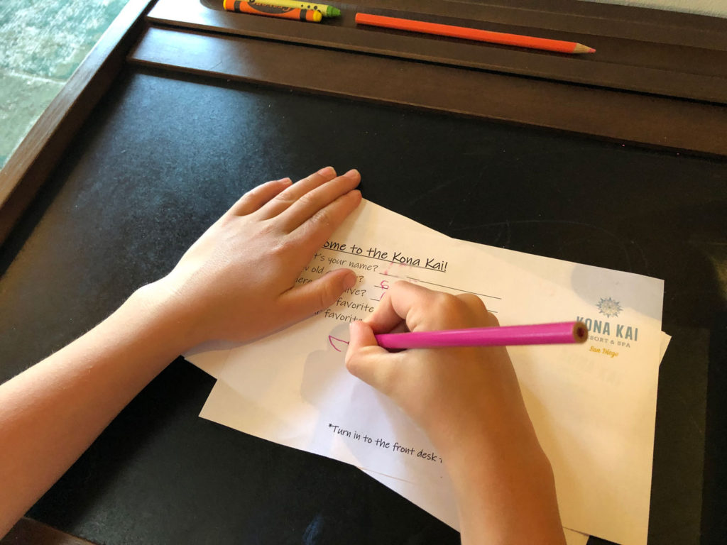 """Our son completes the form for the """"Kids Check In"""" at Kona Kai Resort."""