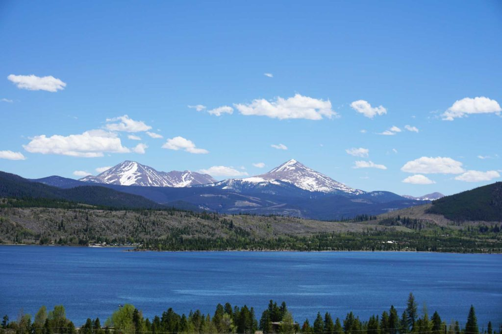 Dillon Reservoir in the summer, with snowcapped mountains in the background.