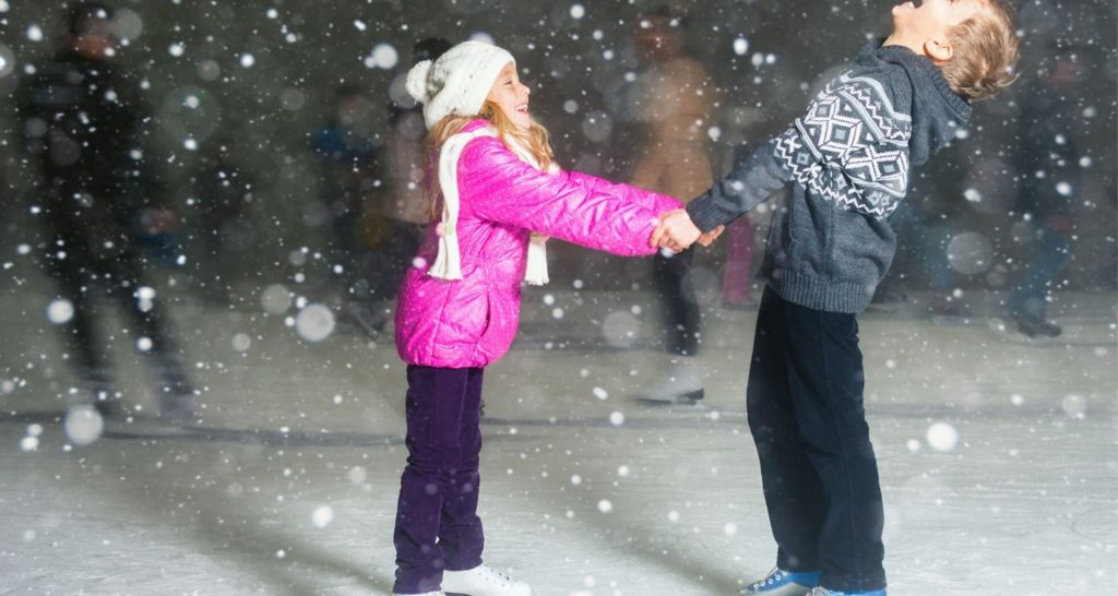 Two children enjoying ice skating as snow flakes drift down from above
