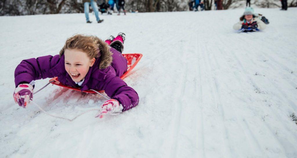 child smiling wihle sledding