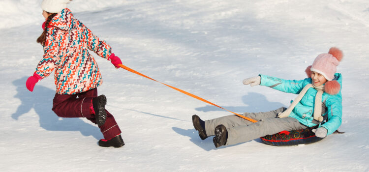 girls enjoying winter park sledding in colorado