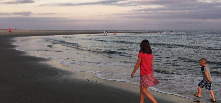 kids walkong on east beach st simons at dusk